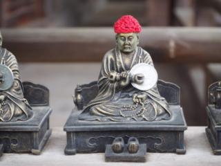 petit bouddha avec un bonnet rouge