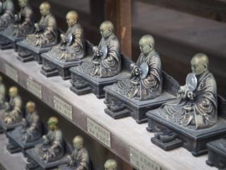 statuette de bouddha avec une pièce en offrande
